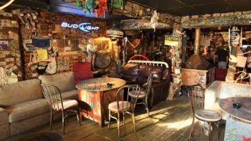 Interior of a Beach Dive Bar with license plates, neon signs and dollar bills stuck to the wall