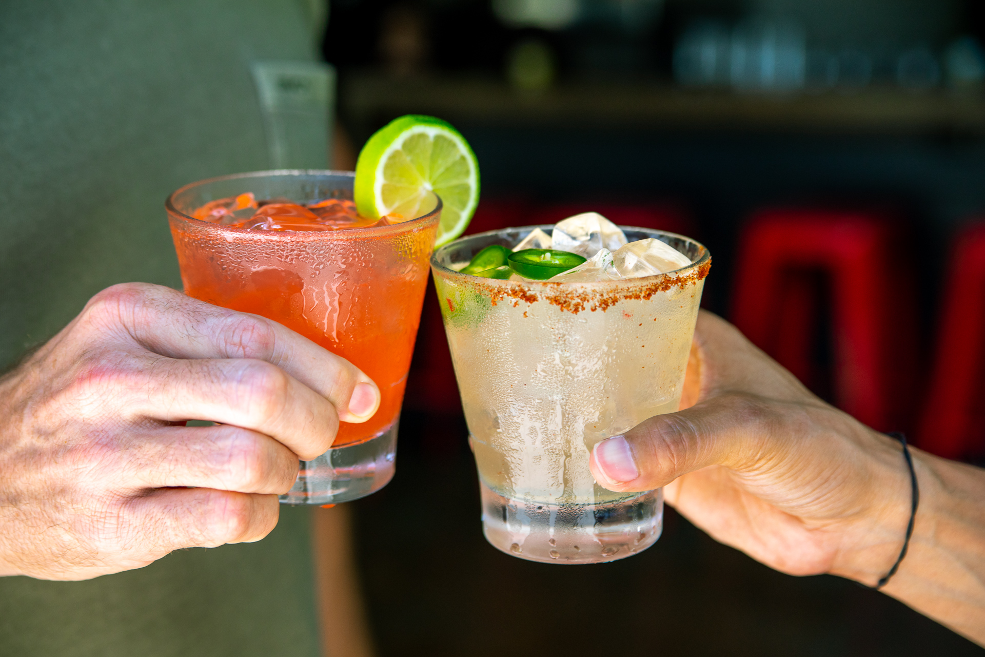 Two margaritas being held together in a cheers by two people