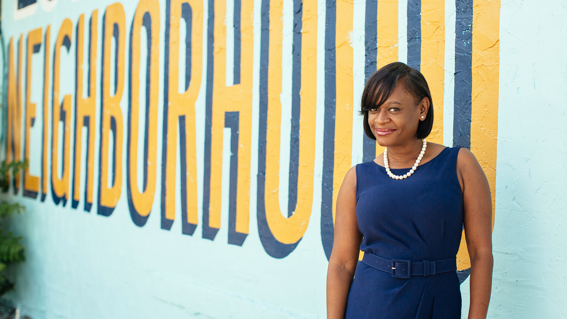 """Deputy Mayor Kanika Tomalin stands in front of a blue wall with the word """"neighborhood"""" written in yellow."""