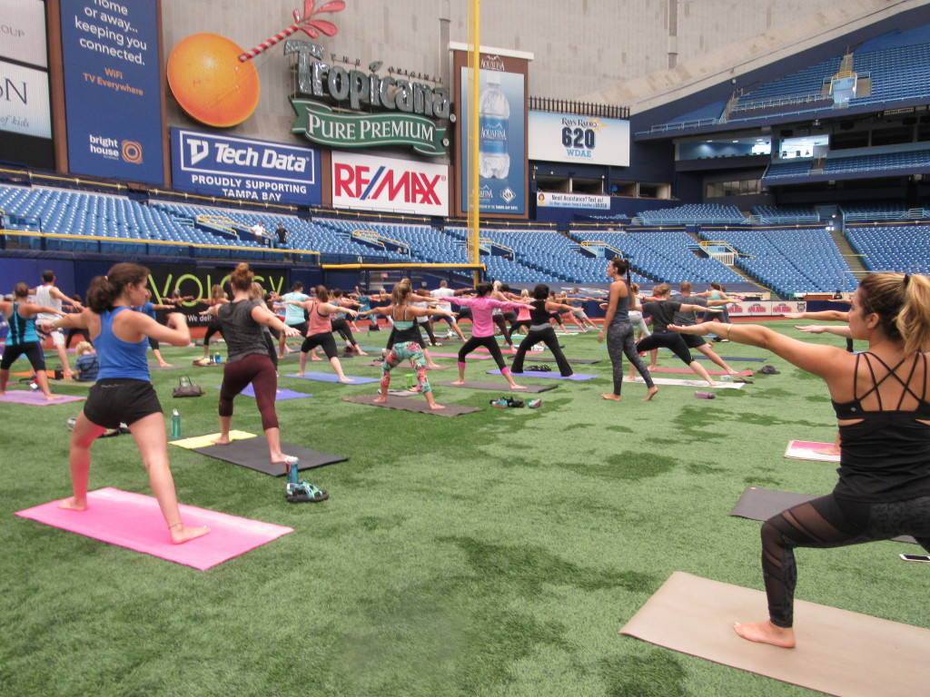 A crowd practicing yoga on the outfield of Tropicana Field