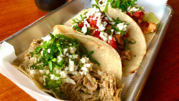 Three tacos in corn tortillas topped with cilantro and queso fresco from Casita Taqueria