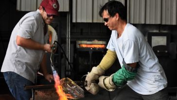 Photo of two artists bending glass with a torch