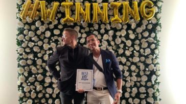 "Photo of Best Blogger winners against a floral wall with an inflatable sign that reads ""winning"""