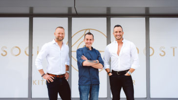 Photo of Rob Bowen, Robert Hesse, and Jason Teabout in front of white and gold banner for new restaurant