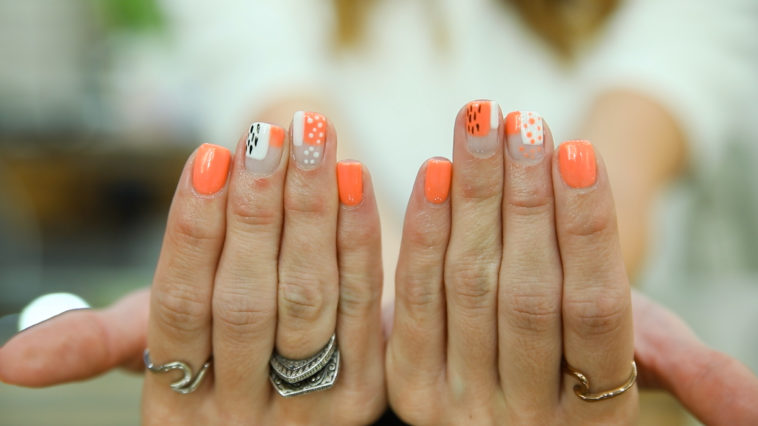 Woman's hands displaying orange and white nail art