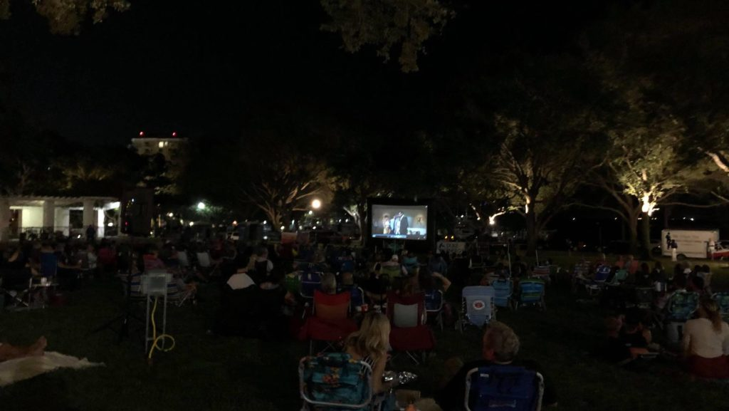 People watching a movie outdoors in the park