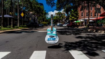 An acoustic guitar in the middle of the road