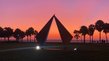 Photo of a triangular sculpture on the waterfront at sunrise.