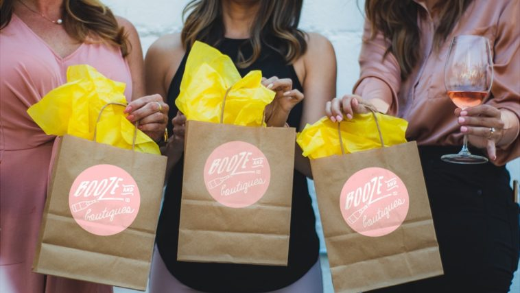 Photo of three paper shopping bags with tissue paper sticking out