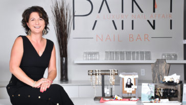 Photo of a nail bar owner posing in front of the front desk