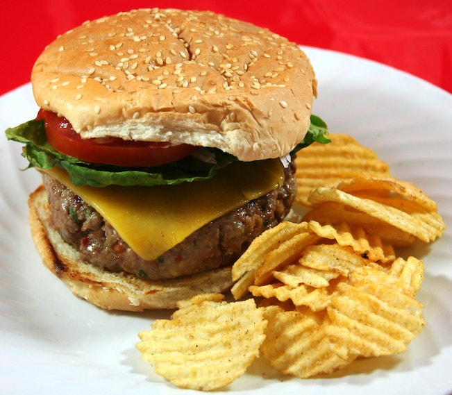 Photo of a large cheeseburger with potato chips