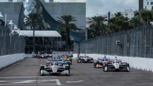 A group of IndyCars race down a track in front of the glass atrium of a museum