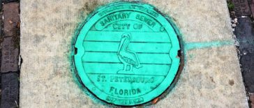 Photo of a bright green manhole cover in downtown St. Petersburg