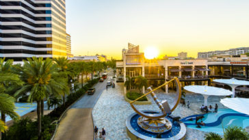 Photo of a sunrise over a shopping plaza with a giant sundial at the center