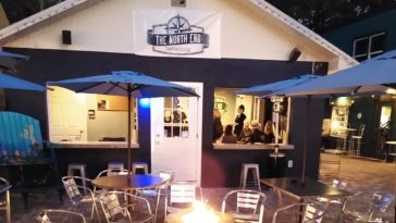 Exterior of a blue and white tap house with a fire pit out front