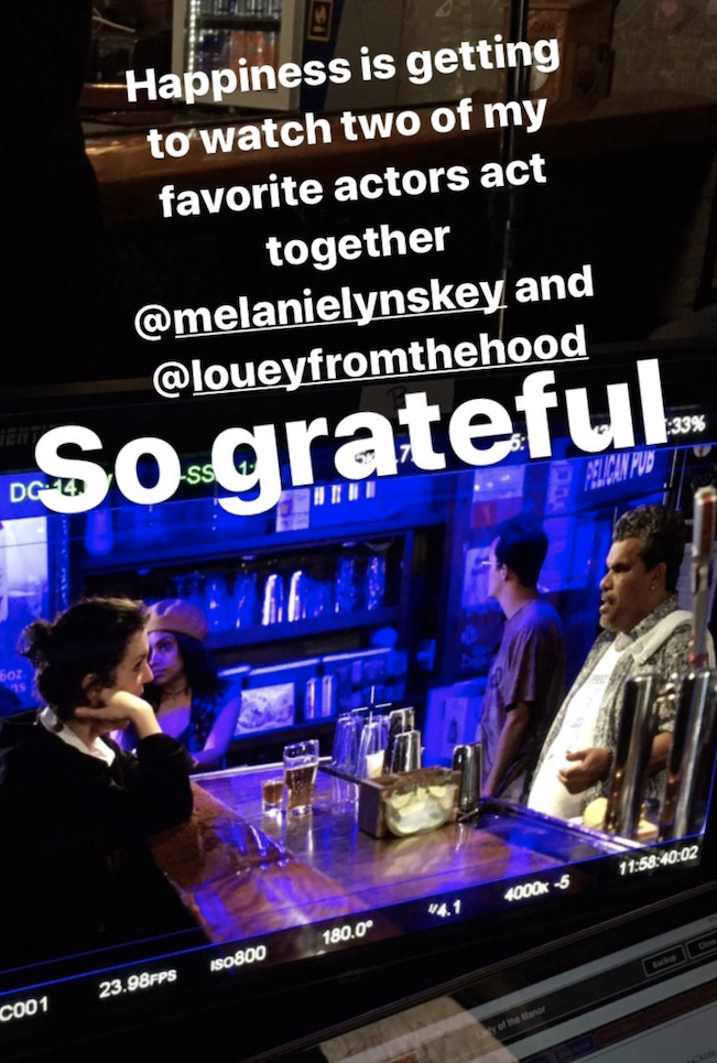 Two actors on set at a bar