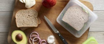 Image of sandwich in a reusable food bag with all the ingredients on the counter