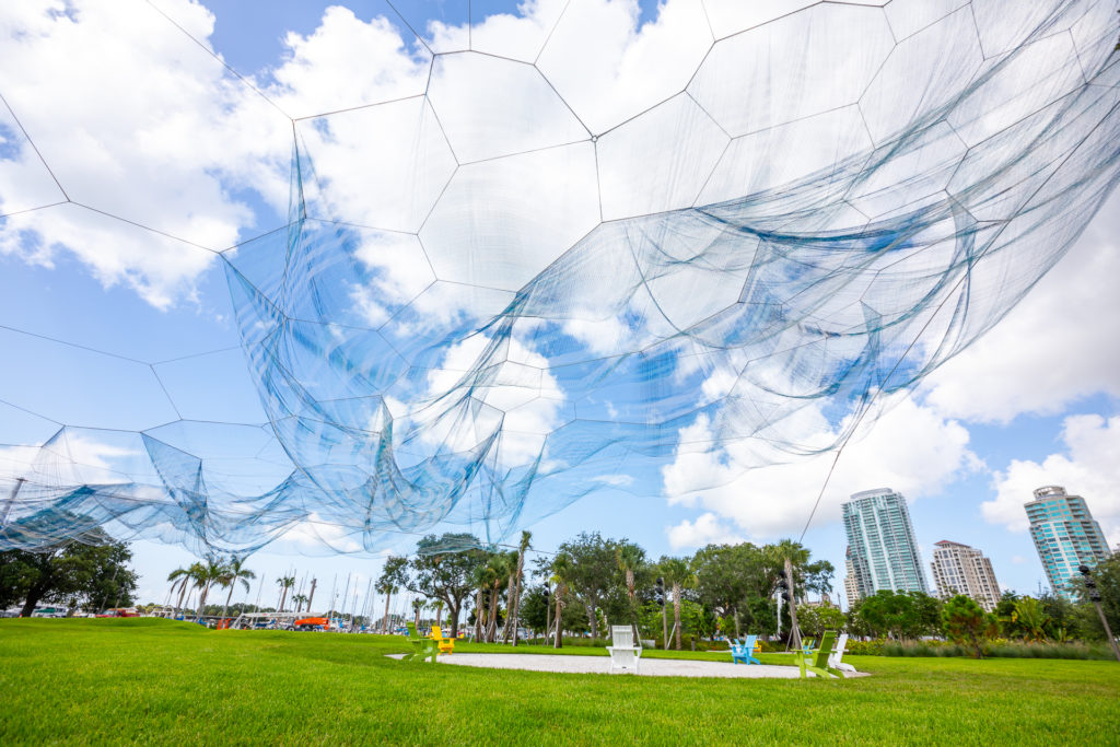A large net art installation over a large patch of green space
