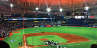 The inside of Tropicana Field, home of the baseball team the Tampa Bay Rays. Lit with orange ceiling and green grass after a game
