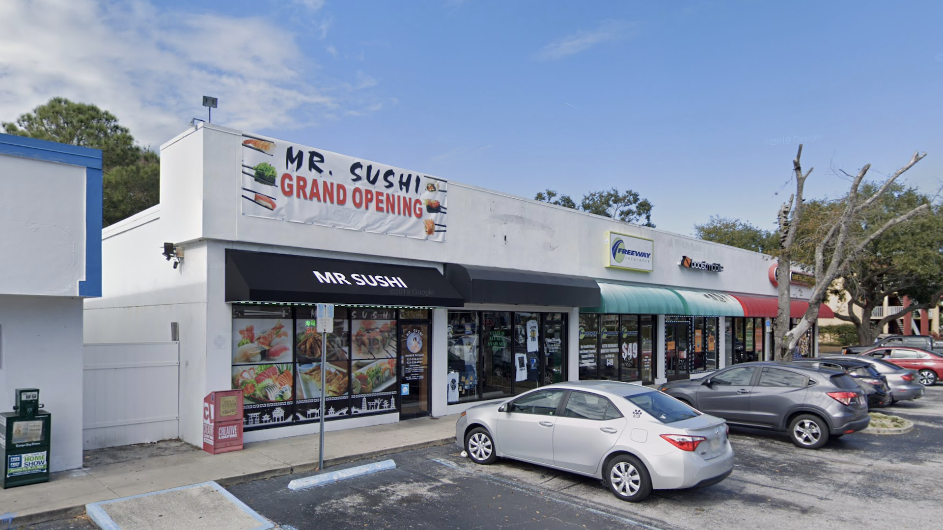 Exterior of a Strip Mall with a Sushi Banner, and several cars parked out front
