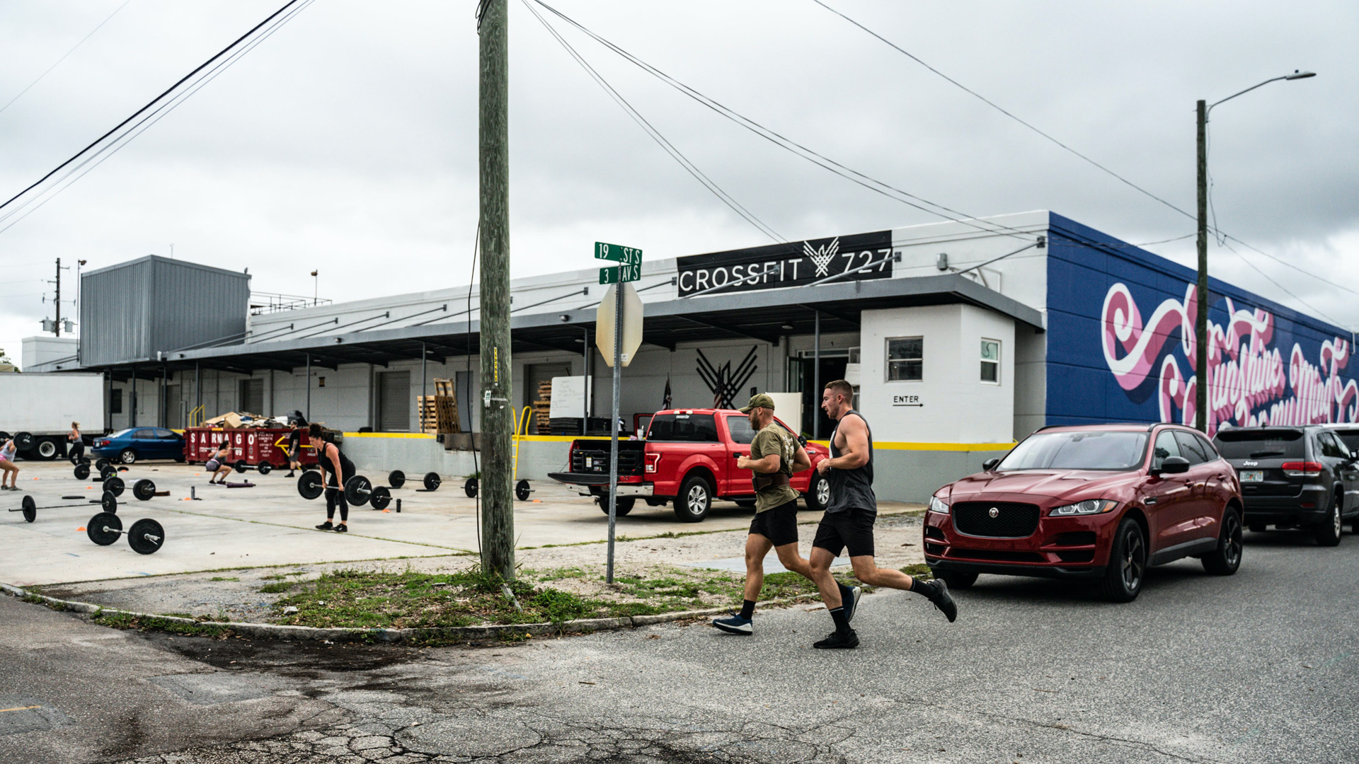 Two CrossFit members running outside next to a blue and pink mural