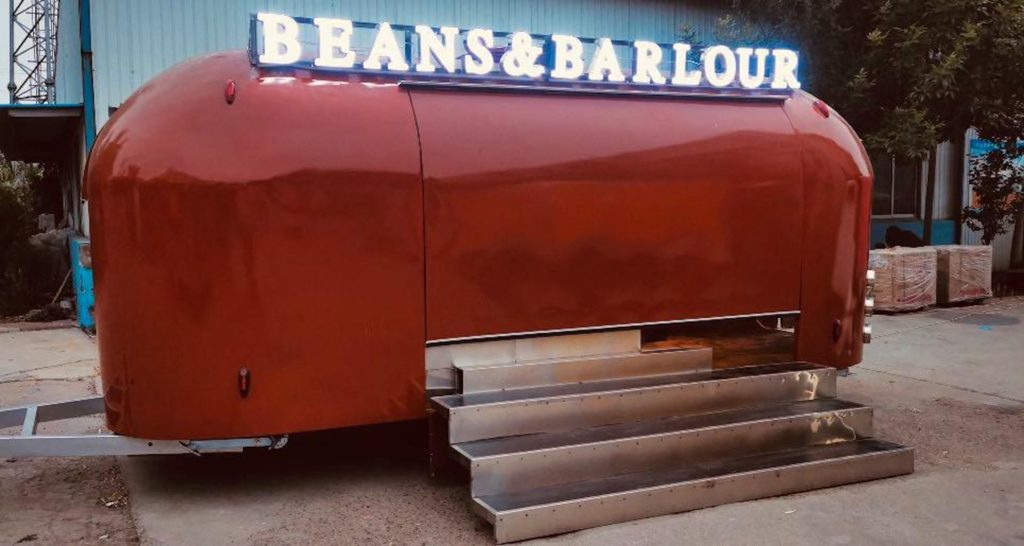 Photo of a red mobile bar with the words Beans and Barlour on top