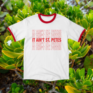 it ain't st. pete's white t-shirt with red ringer collar and sleeves on a background of greenery
