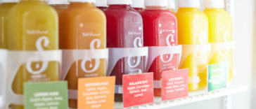 Assorted bottles of cold press juices ranging from green to yellow