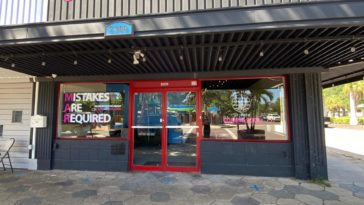 Exterior of an art venue with red doors and a black facade