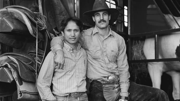A black and white photograph of two cowboys. The one on the right is wearing a cowboy hat and has his arm around the shoulder of the other cowboy.