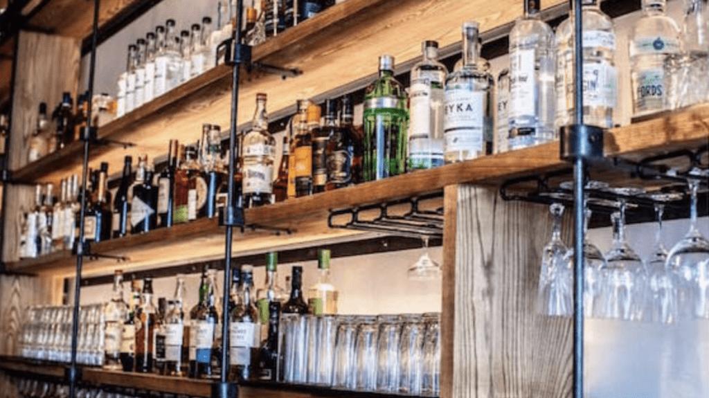 Photo behind a bar featuring liquor bottles