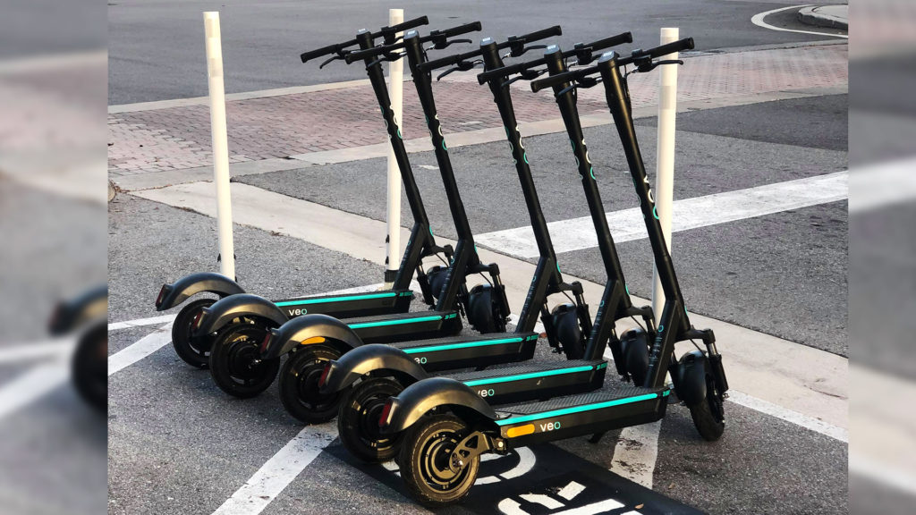 Five e-scooters side by side in a parking spot