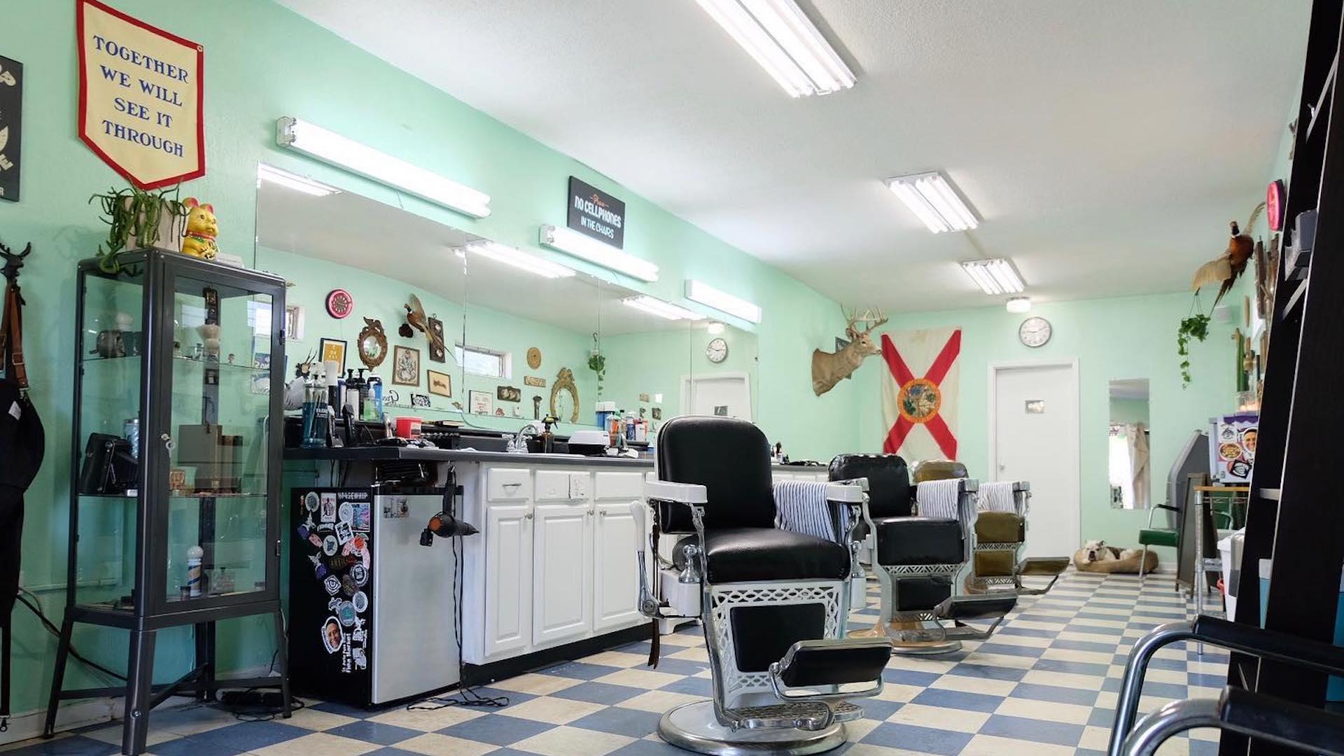 Interior of a barbershop with leather chairs and green walls
