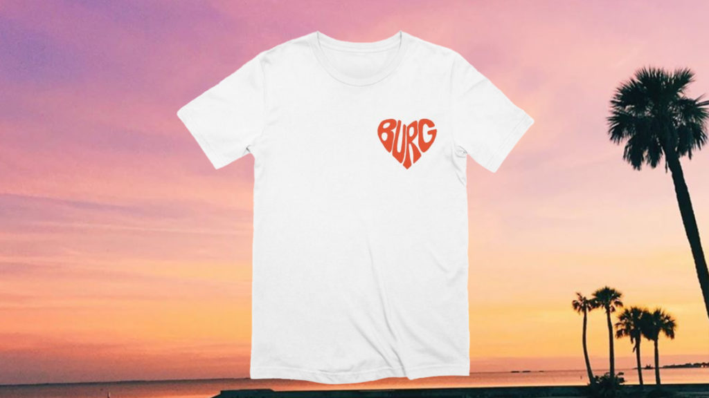 "white shirt with red ""burg"" text in shape of heart on a photo of a sunset in the background"
