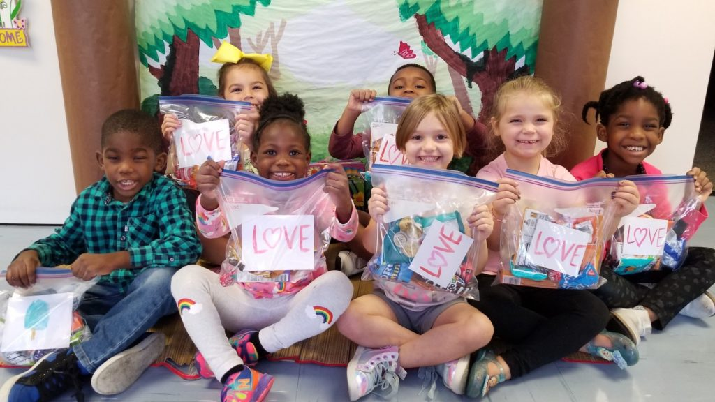 Smiling kids holding small goodie bags with love written on them