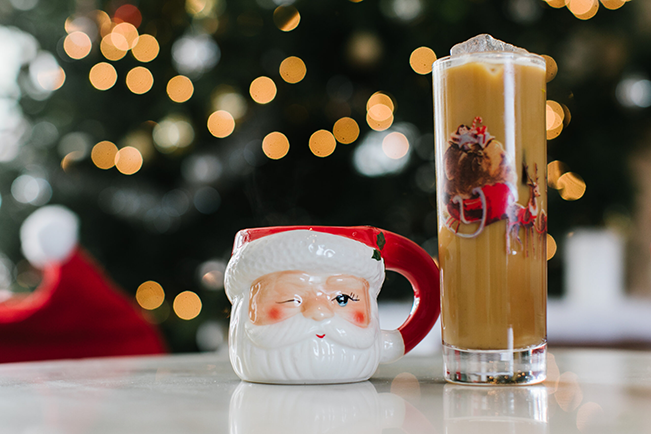 Santa mug situated next to a tall, skinny cocktail glass.