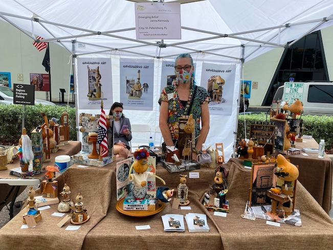 Assorted sculptures and craft art pieces displayed under a tent