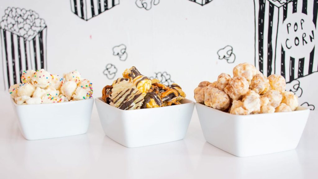 Image of three different gourmet popcorns in white bowls