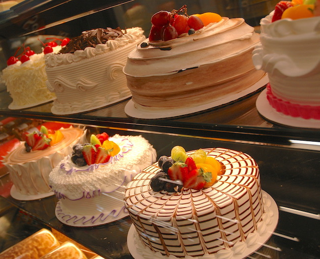 Assortment of cakes behind glass in a grocery store