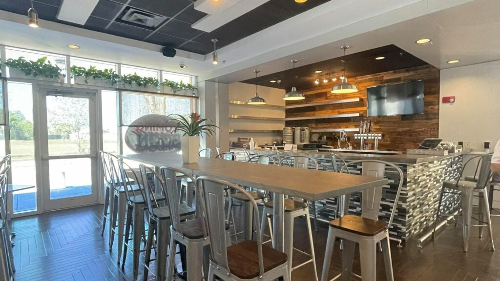 wrap around bar and tall steel chairs around a long wooden table