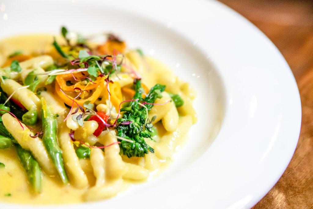 photo of a pasta dish with fresh greens on top