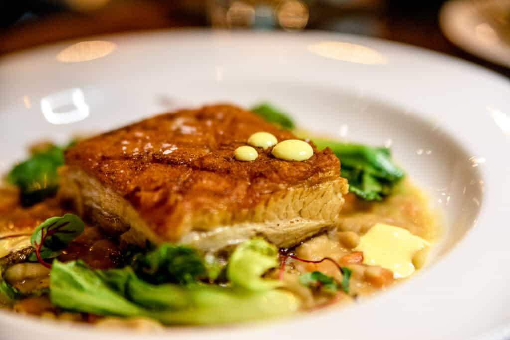 a pork dish over fresh greens