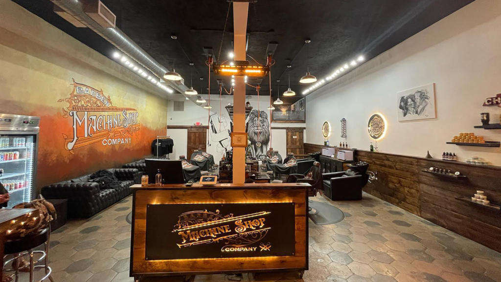 Inside a barbershop with a lion mural in the back