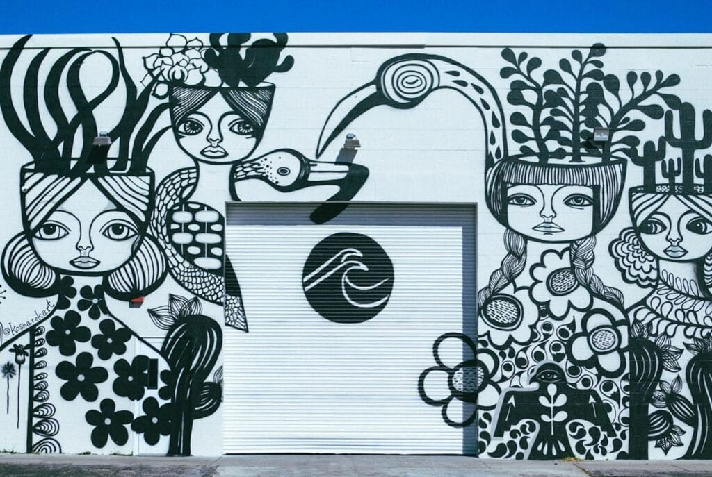 exterior of an arts warehouse with a large black and white mural on the front