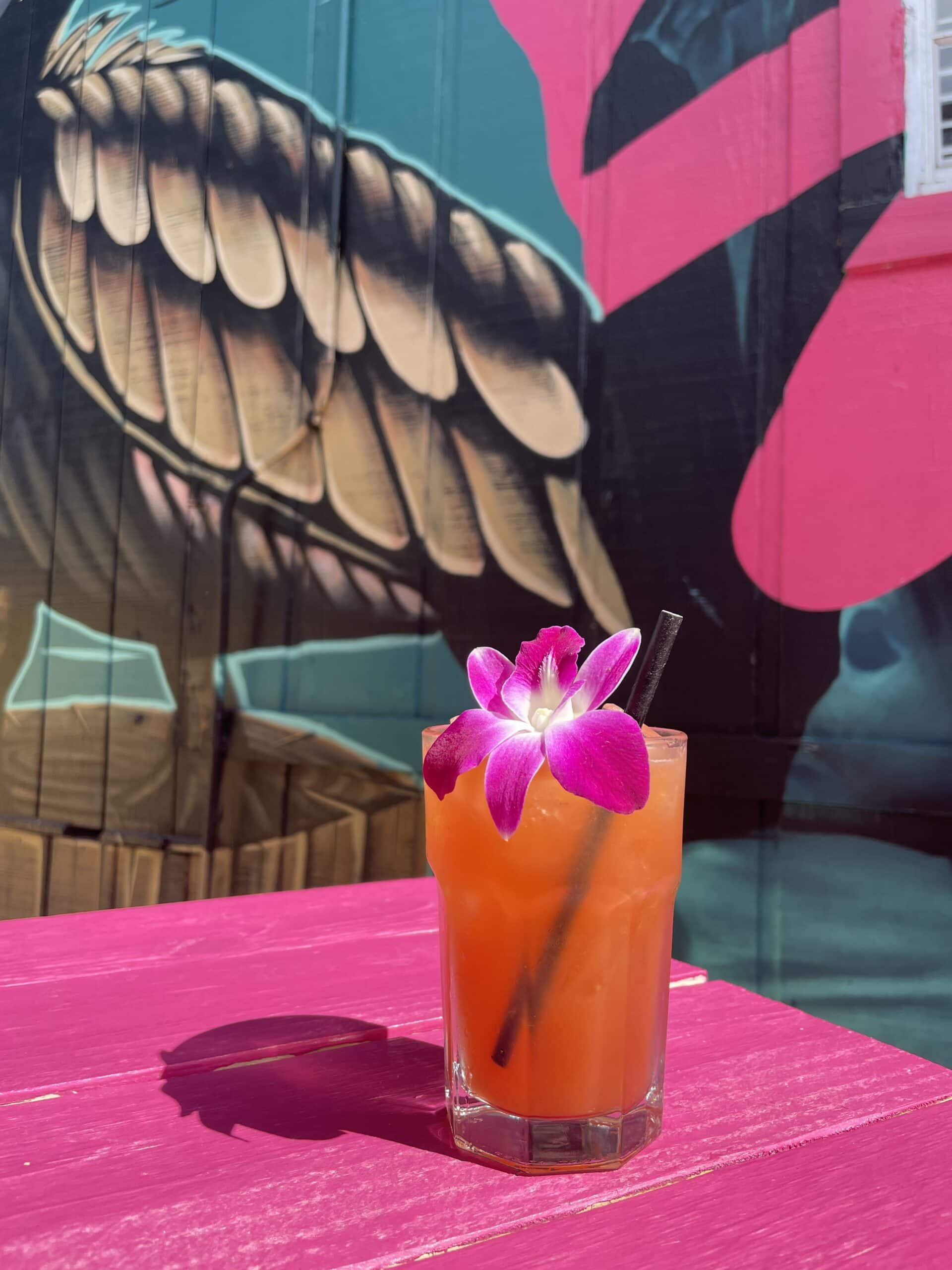 Image of red-colored cocktail in glass with purple orchid in front of colorful mural.