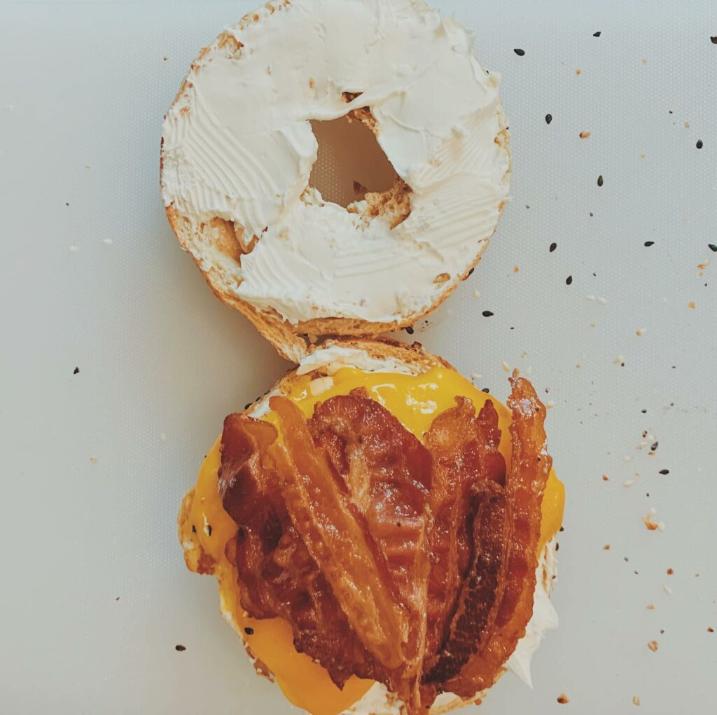Open face bagel with bacon and cream cheese.