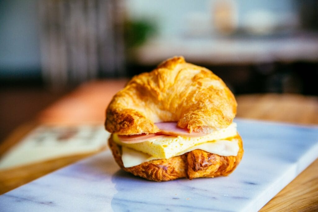 a croissant sandwich with eggs and ham on a plate.