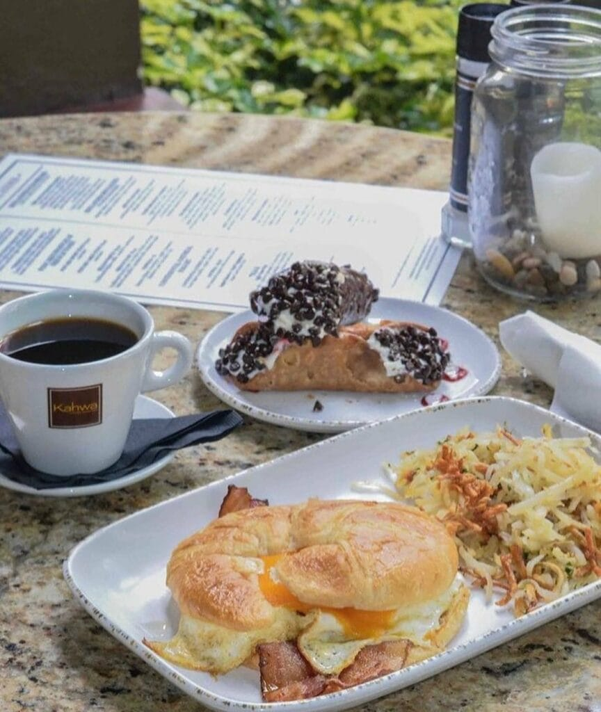 coffee, a croissant sandwich, cannoli and hash browns arranged on a plate.