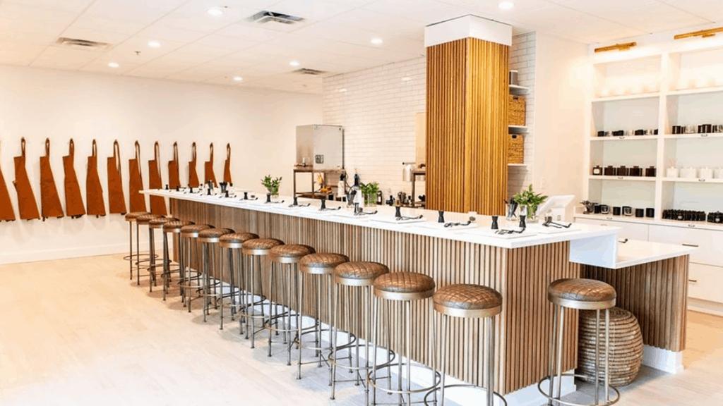 inside a candle shop with a large white bar and bar stools