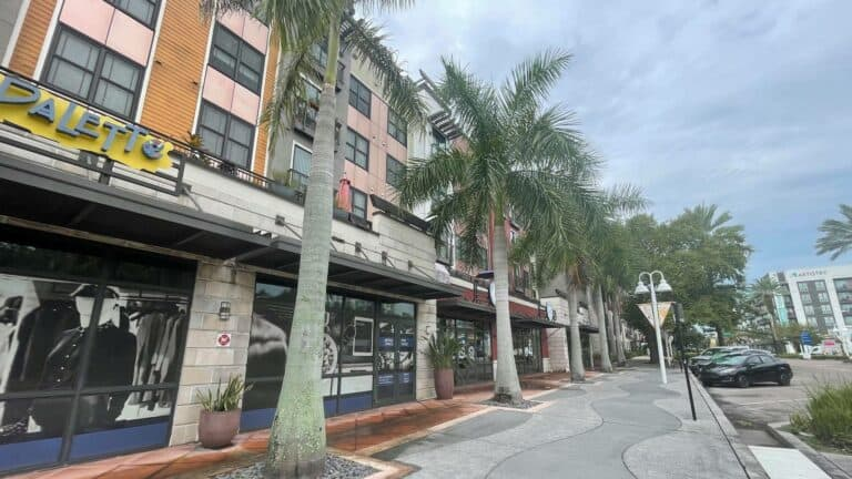 exterior of a brick building with a pedestrian walkway and palm trees out front